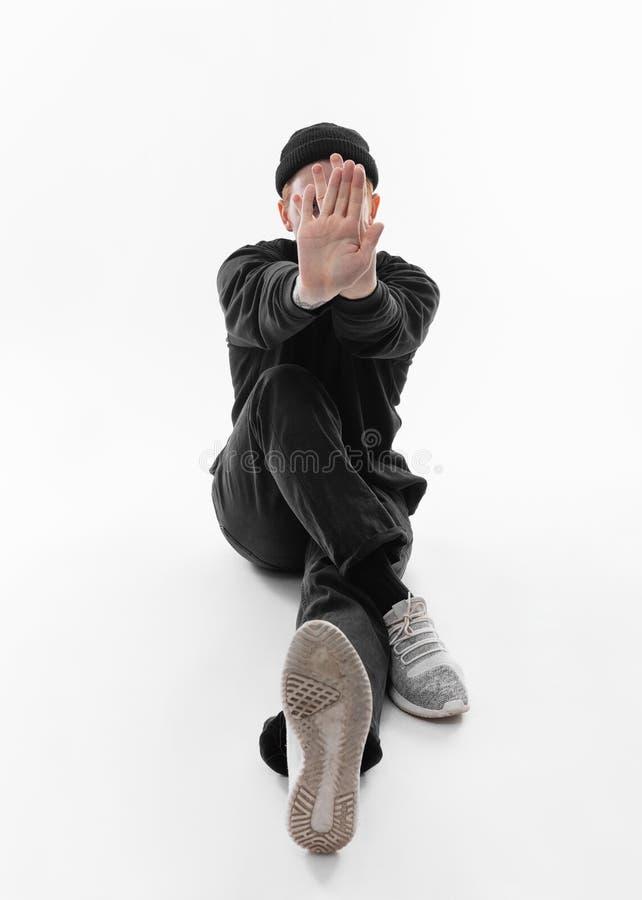 在黑牛仔裤、运动衫、帽子和灰色运动鞋打扮的自由式舞蹈家在演播室跳舞在地板上的开会 库存图片
