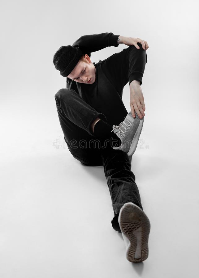 在黑牛仔裤、运动衫、帽子和灰色运动鞋打扮的自由式舞蹈家在演播室跳舞在地板上的开会 免版税图库摄影