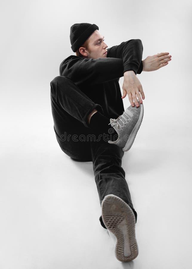 在黑牛仔裤、运动衫、帽子和灰色运动鞋打扮的自由式舞蹈家在演播室跳舞在地板上的开会 图库摄影