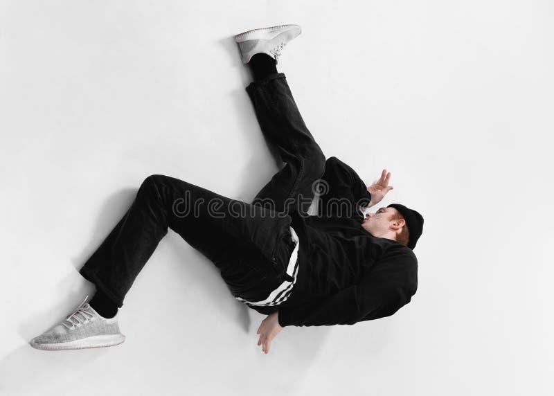 在黑牛仔裤、运动衫、帽子和灰色运动鞋打扮的自由式舞蹈家在演播室跳舞说谎在地板上 免版税库存照片