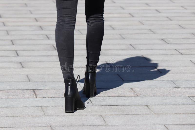 在黑牛仔裤和鞋子的亭亭玉立的女性腿在高跟鞋,在路面的阴影 免版税库存照片
