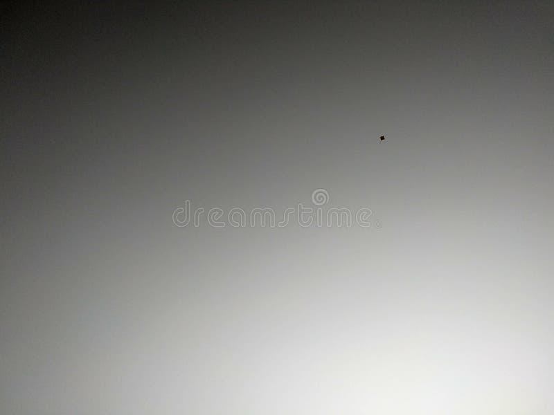 在黑白天空的小风筝 免版税库存图片