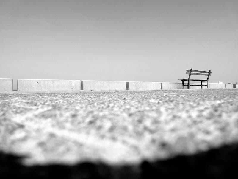 在黑白的孑然-面对无限的一条空的长凳 免版税库存图片