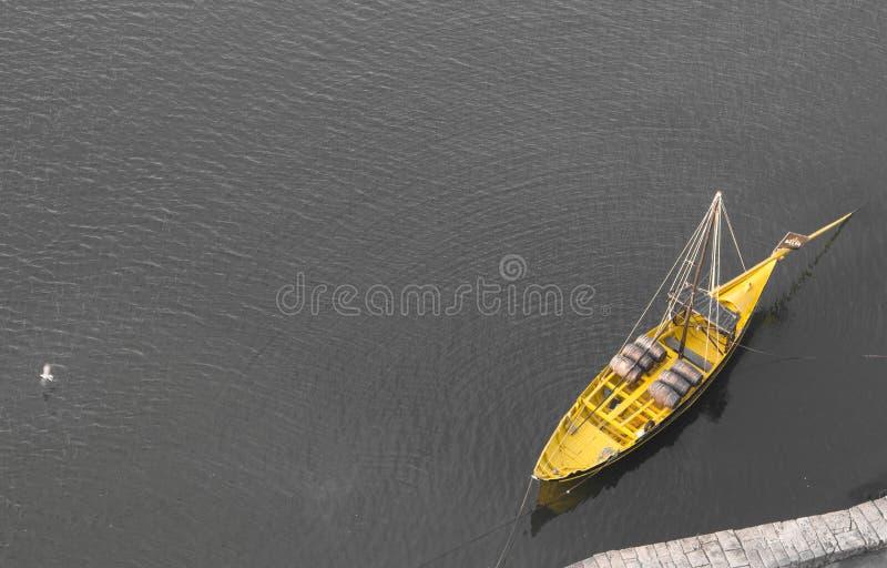 在黑白背景的黄色小船 有葡萄酒桶的黄色小船从上面观看 在水上面鸟瞰图的小船 图库摄影