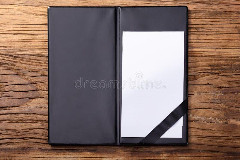 在黑皮革文件夹的空白空的白皮书 图库摄影