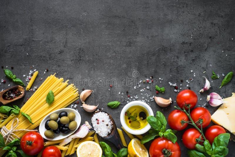 在黑石桌上的意大利食物背景 顶视图 库存照片