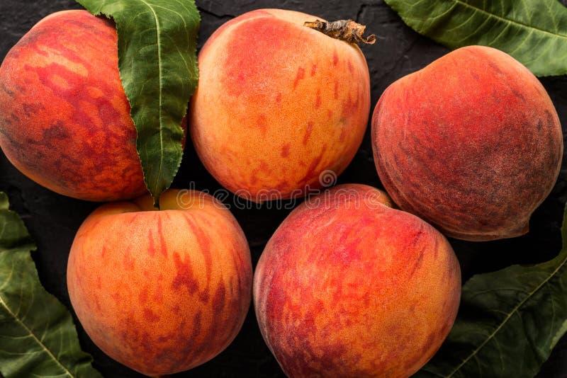 在黑石背景的成熟桃子 健康概念的食物 免版税库存照片