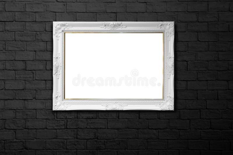 在黑砖墙上的白色框架 库存照片