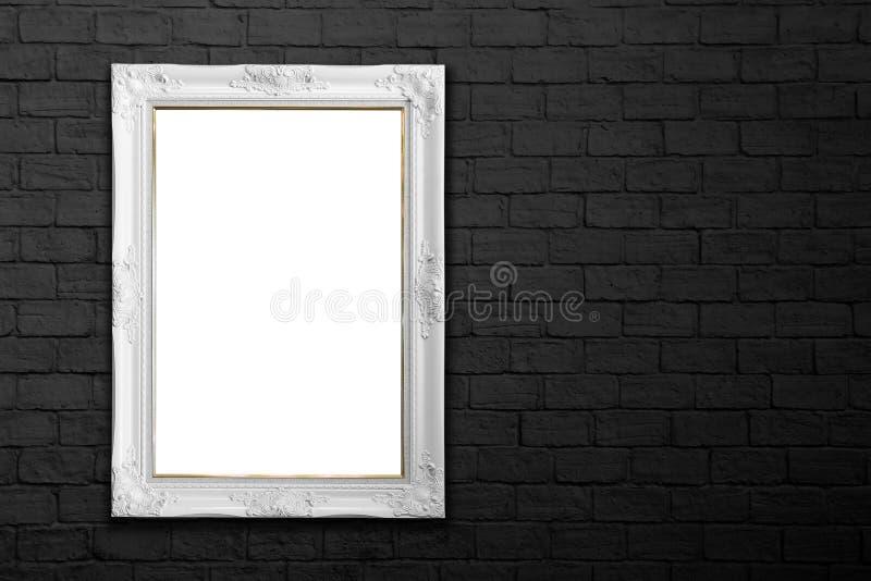 在黑砖墙上的白色框架 免版税图库摄影
