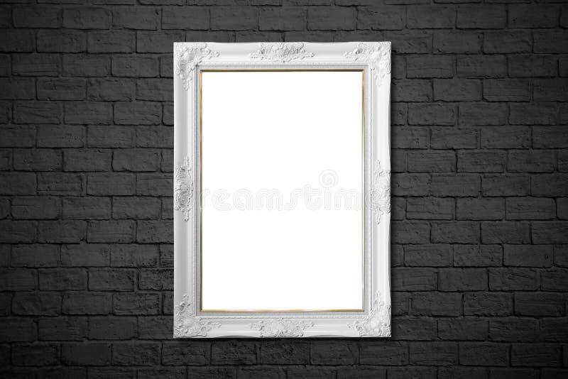 在黑砖墙上的白色框架 免版税库存图片