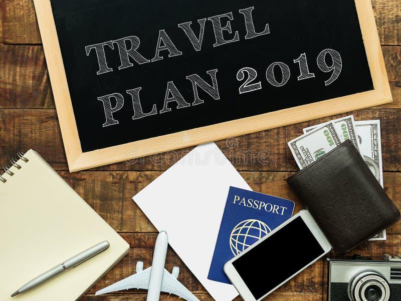 在黑粉笔板的旅游计划2019词用移动的项目装饰 旅行计划概念 免版税库存图片