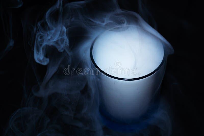 在黑织品背景的白色烟在玻璃 烟延长了背景 Vaping文化,没有香烟的生活 图库摄影