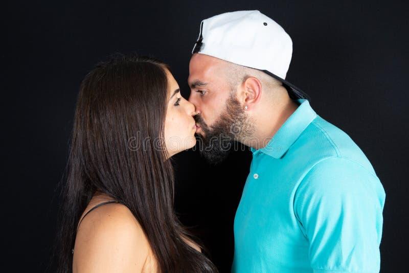 在黑背景中隔绝的美好的愉快的夫妇亲吻特写镜头画象 库存图片