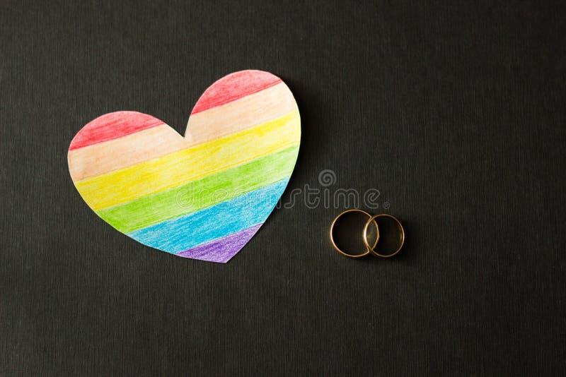 在黑背景和心脏的婚戒以旗子lgbt,同性婚姻,同性恋的形式 免版税库存图片
