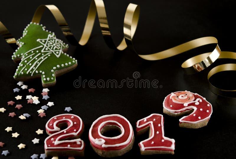 在黑背景姜饼红色第2019年与多彩多姿的星,绿色姜饼冷杉的新年卡片 免版税库存图片