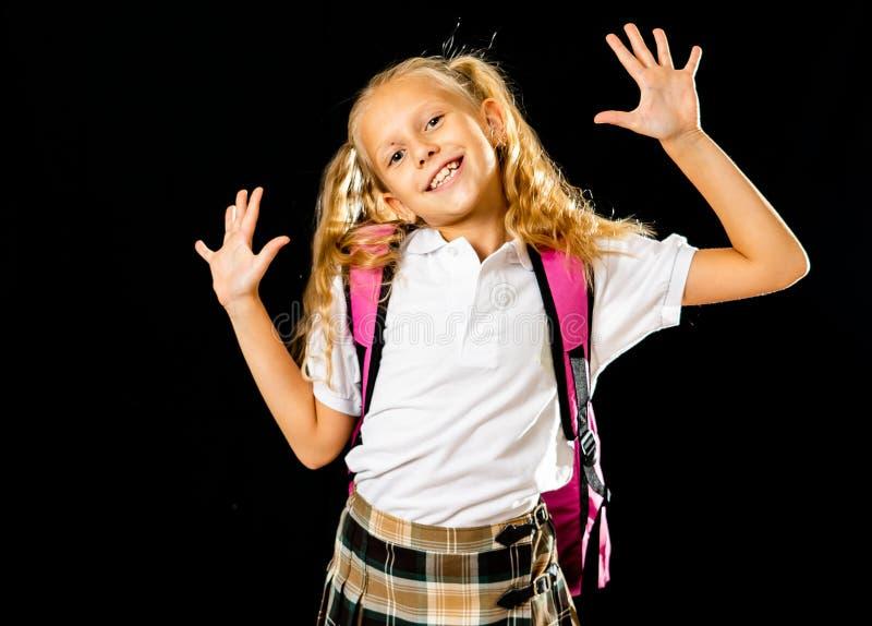 在黑背景有大桃红色书包的可爱的美丽的矮小的女小学生感到激动和愉快隔绝的回到 库存图片