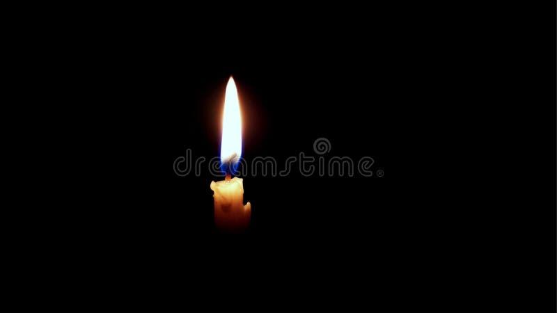 在黑背景的一个小被点燃的红色蜡烛 免版税库存照片