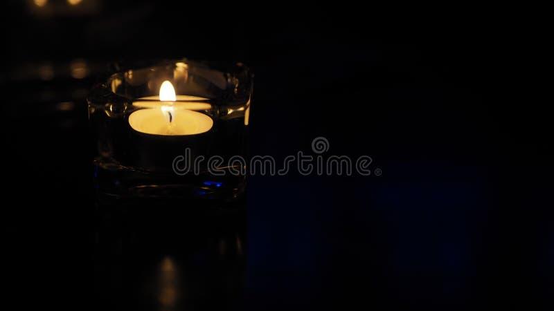 在黑背景的一个蜡烛,在桌上的tealight 免版税库存照片