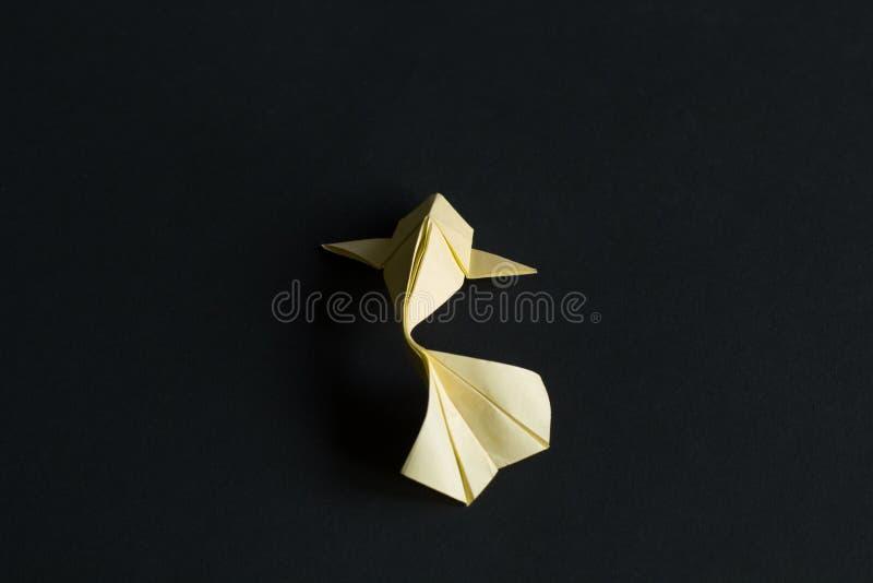 在黑背景的一条手工纸工艺origami淡黄色koi鲤鱼鱼 r 免版税库存图片