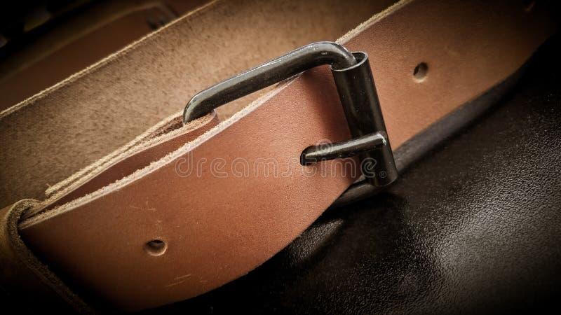 在黑背景的一条美丽的棕色手工制造皮革照相机吊索皮带 库存图片