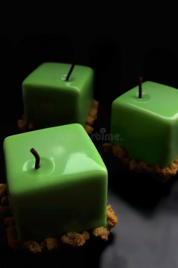 在黑背景的三个绿色苹果发光的给上釉的立方体点心 免版税图库摄影