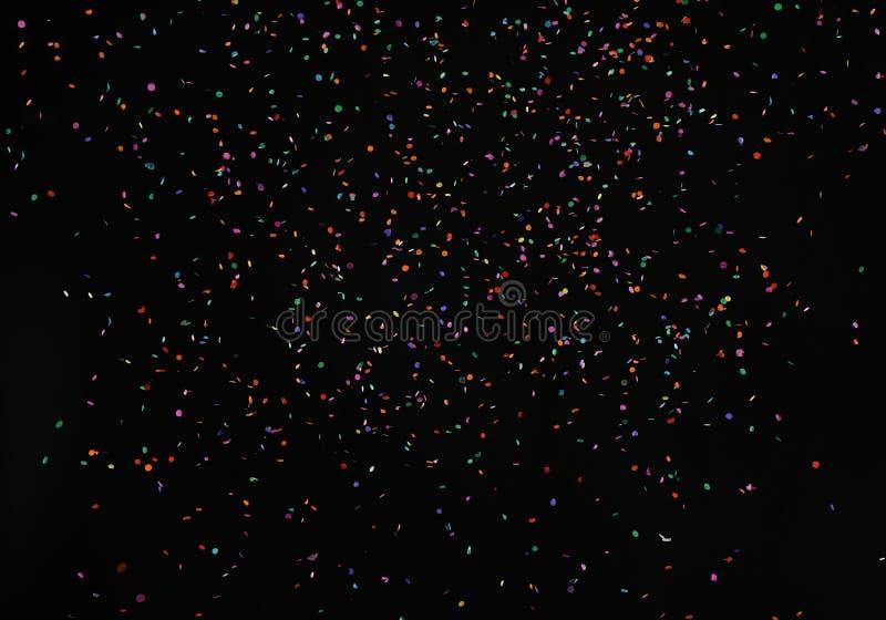 在黑背景的下跌的发光的五颜六色的微粒五彩纸屑闪烁纹理 图库摄影