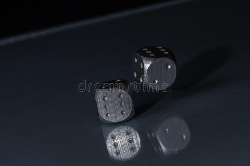 在黑背景的两个滚动的钢银色赌博娱乐场模子与蓝色底部 免版税图库摄影