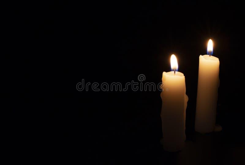 在黑背景的两个蜡烛 在黑暗中点燃蜡烛 与温暖的火焰的黄色蜡蜡烛 在memoriam横幅 免版税库存照片