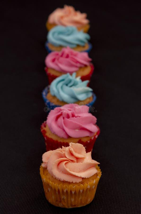 在黑背景的五颜六色的自创杯形蛋糕 免版税图库摄影