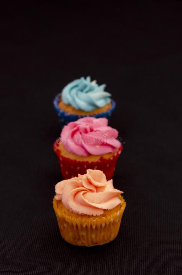 在黑背景的五颜六色的自创杯形蛋糕 库存照片