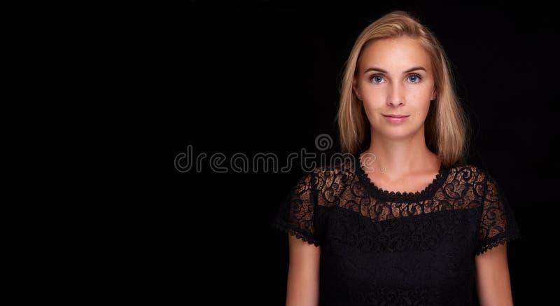 在黑背景的俏丽的妇女 库存照片