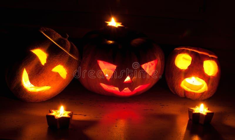 在黑背景的可怕万圣夜南瓜和瓜起重器o灯笼点燃了与小在周围和星蜡烛 免版税库存图片