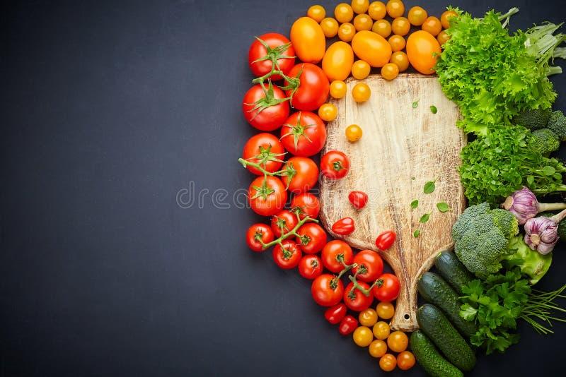 在黑背景的各种各样的五颜六色的菜围拢的空的木切板 免版税库存图片