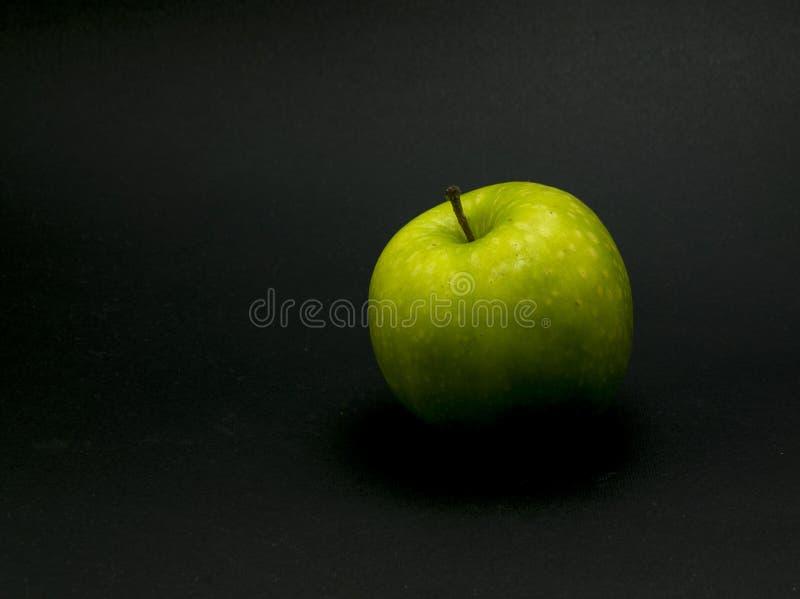在黑背景的唯一绿色苹果 库存图片