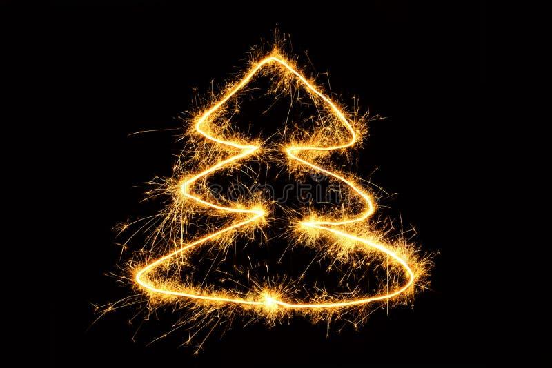 在黑背景的圣诞树画的闪耀的闪烁发光物 免版税库存照片