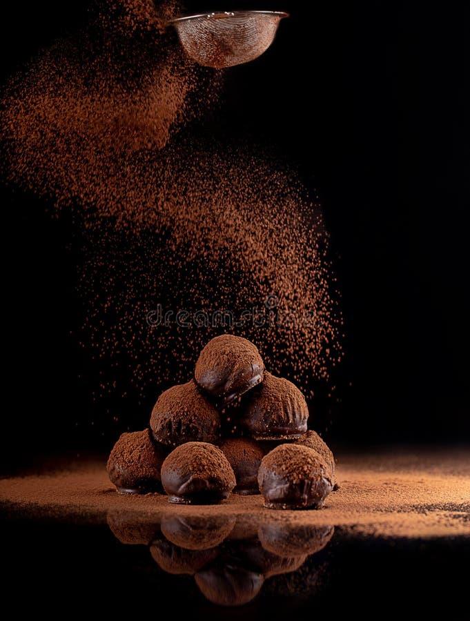 在黑背景的块菌状巧克力 库存照片