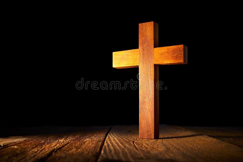 在黑背景的基督徒木十字架 免版税库存照片