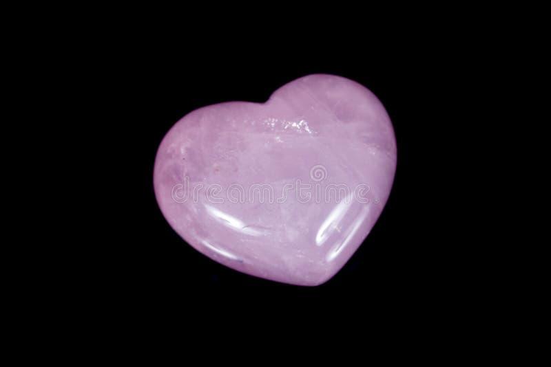 在黑背景的宏观矿物石心脏桃红色石英 免版税库存照片