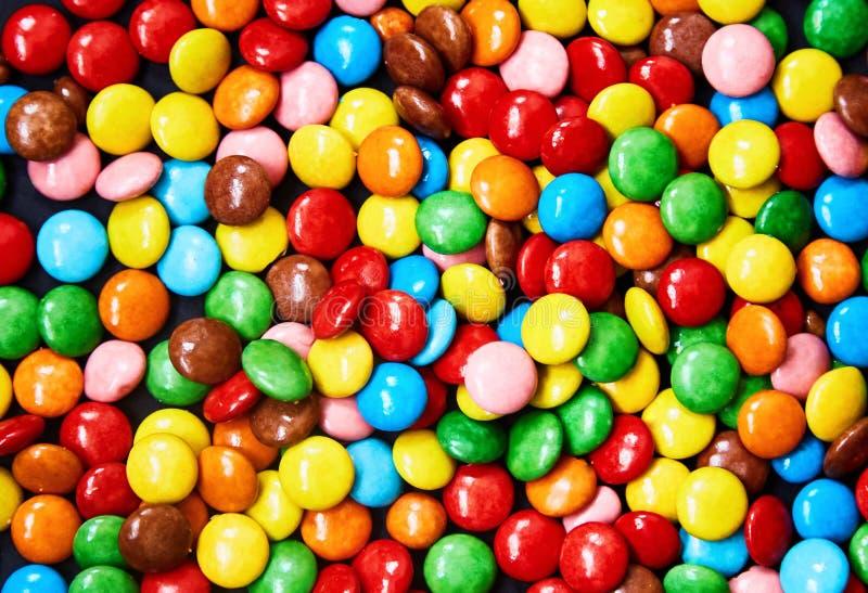 在黑背景的小五颜六色的糖果 免版税库存图片