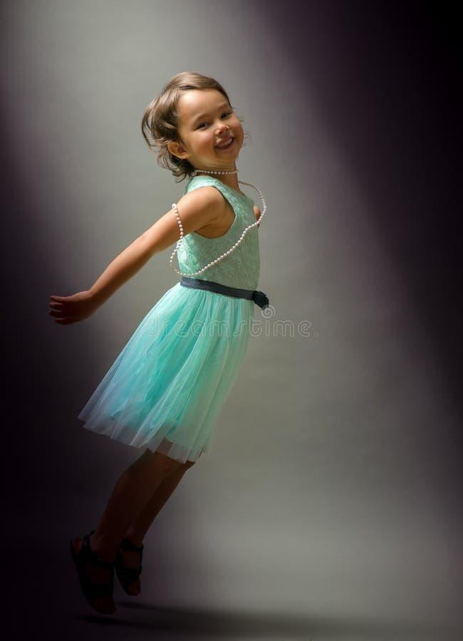 在黑背景的小的逗人喜爱的女孩跳舞 图库摄影