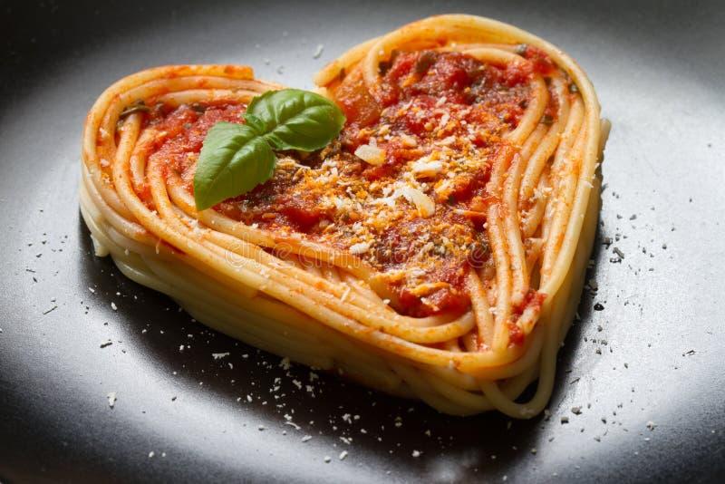 在黑背景的意粉面团心脏爱意大利食物的饮食摘要概念 免版税库存图片