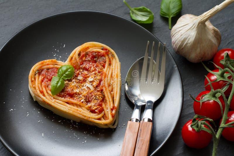 在黑背景的意粉面团心脏爱意大利食物的饮食摘要概念 免版税库存照片