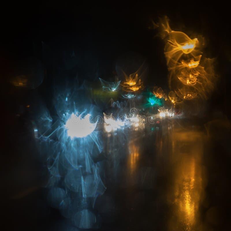 在黑背景的抽象光蓝色、黄色和白色 夜视图城市在雨中 库存图片