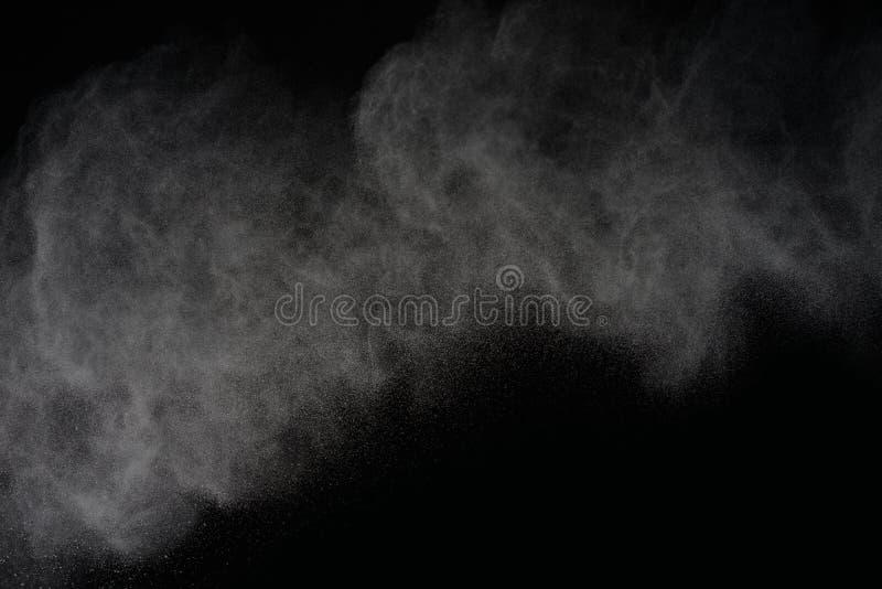 在黑背景的抽象派白色粉末 结冰行动  库存照片