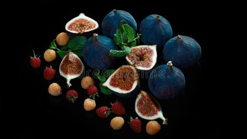 在黑背景的新鲜的蓝色无花果 美丽的紫罗兰色无花果用用红色和黄色莓莓果 复制空间 关闭 库存照片