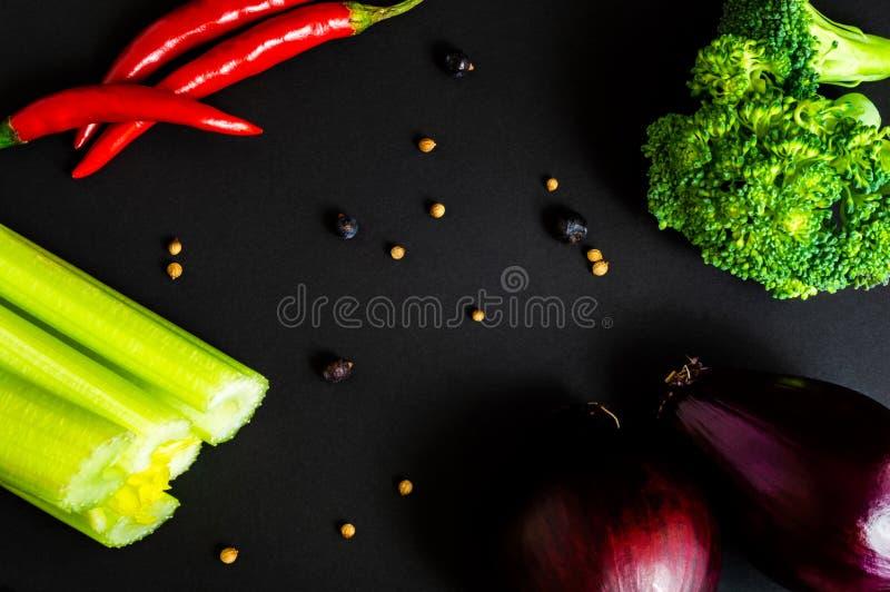 在黑背景的新鲜蔬菜:硬花甘蓝,芹菜,红洋葱,辣椒 不同的香料 健康的食物 平位置,顶视图 免版税库存照片