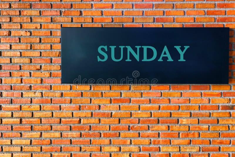 在黑背景的星期天信件与砖墙 库存照片