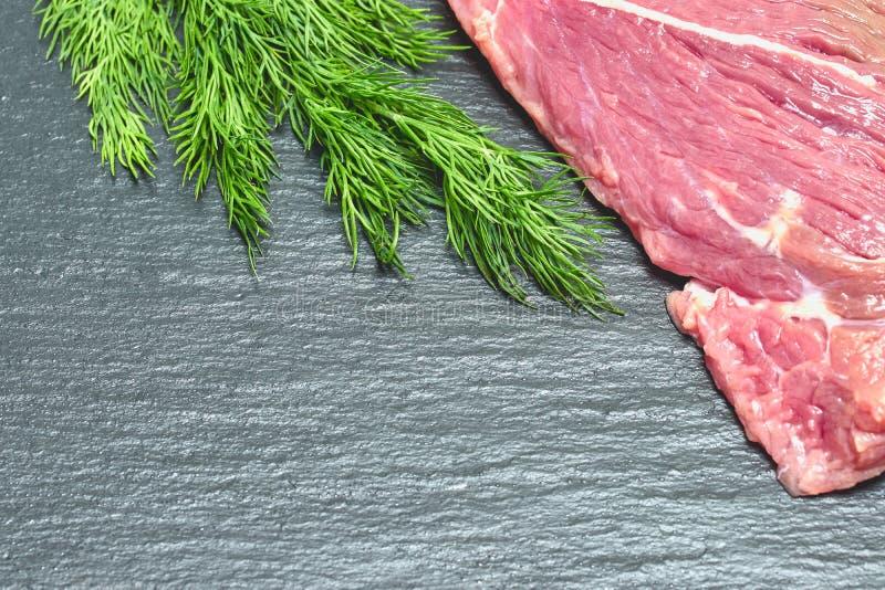 在黑背景的未加工的新鲜的牛肉肉与莳萝小树枝  库存图片