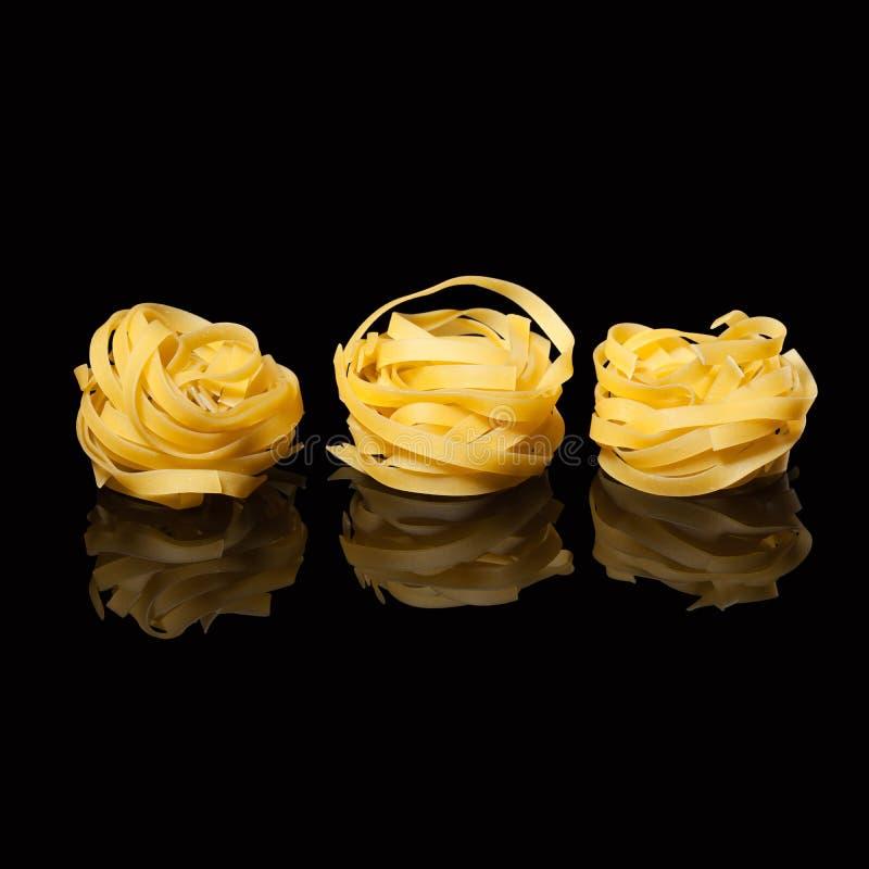 在黑背景的未加工的未煮过的tagliatelle巢与反射 传统意大利的意大利面食 库存照片