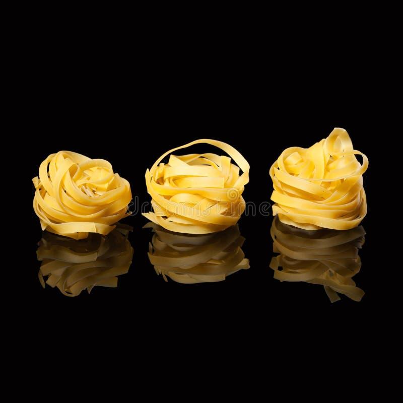 在黑背景的未加工的未煮过的tagliatelle巢与反射 传统意大利的意大利面食 库存图片